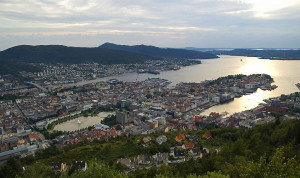 «Fløyen view on Bergen edit» av Tomoyoshi NOGUCHI from OSLO, NORWAY (edit by Aqwis) - Bergen over view. Lisensiert under CC BY 2.0 via Wikimedia Commons